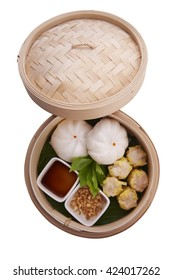 Classic Chinese style Canton cuisine - pork steamed dumpling or dim sum along with Chinese bun served in small steamer basket on white background