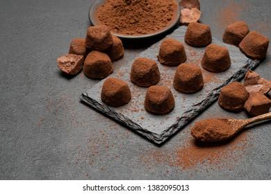 classic chocolate truffles on dark concrete background