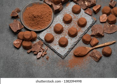 classic chocolate truffles and pieces of chocolate on dark concrete background