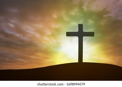 Classic christian cross with on sunset background.