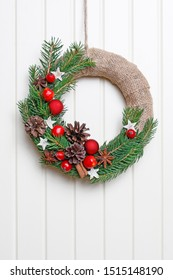 Classic Christmas door wreath with fir twigs, red balls, small apples and cones.