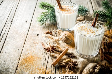 Classic Christmas drink Eggnog, chilean Cola de mono (monkey tail) cocktail, or Puerto Rican Coquito  eggnog, on old wooden background with pine tree branches copy spaces