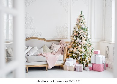 Classic Christmas light interior in white and pink tones with a couch, tree and molding in the Baroque style and renaissance.