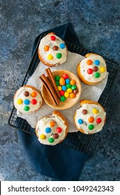 Classic cinnamon rolls - cinnabons with cream cheese frosting with smarties. Blue stone background. Top view.