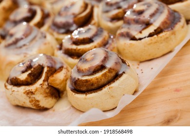Classic cinnamon rolls cinnabons with creamy frosting on baking paper