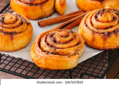 Classic cinnamon rolls - cinnabons won a wire rack. Wooden background.
