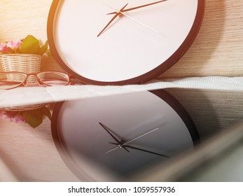 Classic circle clock in ten minutes pass eight and pink roses flower in white basket behind red glasses reflected on mobile phone and on the cotton bed background with sunshine in the morning.