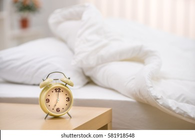 The classic clock on the background of the bed