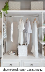 classic closet style with clothes hanging, white color tone wardrobe with clothes, interior decoration design concept