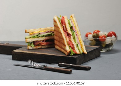 Classic club sandwich with ham and bacon on a wooden board. Next a cup of pickled vegetables. Gray background. Close-up.
