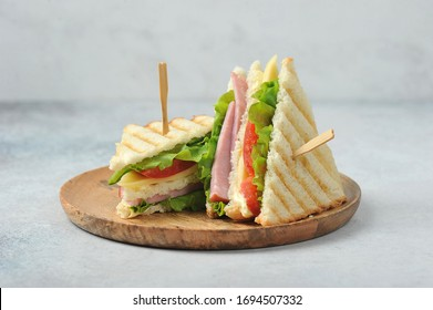 Classic club sandwich on a wooden plate. The sandwich filling includes ham, cheese, lettuce, tomato slices. Light background. Close-up.