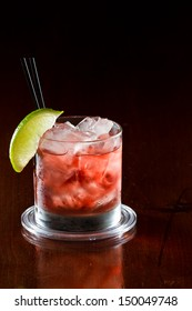 classic cocktail, cape cod served in a glass on a dark bar garnished with a lime