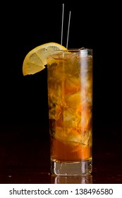 classic cocktail long island iced tea served on a bar and garnished with a lemon slice