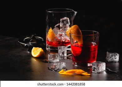 Classic cocktail Negroni with gin, campari, red vermouth. Traditional recipe. Place for writing text, dark background with bar equipment