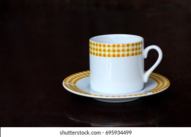 Classic coffee cup and dish on dark wooden table with copy space.