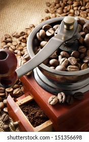 Classic coffee grinder full of coffee beans on a sackcloth background.
