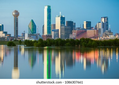 The classic Dallas, Texas skyline at dusk, with reflections in the Trinity River.