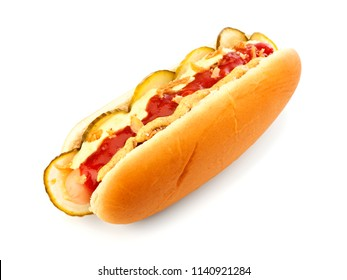 Classic Danish hot dog with ketchup, mustard, cucumber slices and roasted onions isolated on white background