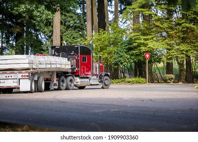Classic dark red long hauler big rig industrial semi truck tractor with low cab and loaded flat bed semi trailer turning from highway road to rest area parking lot for take a brake