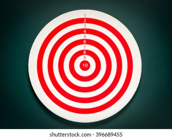 Classic dart target board. Red and white of dartboard on black background.