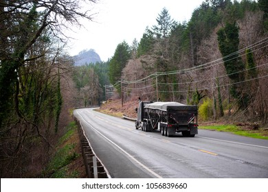 Classic day cab black American big rig semi truck transporting covered by tarp bulk cargo with bulk semi trailer moving on the winding road in winter forest in Columbia Gorge Area