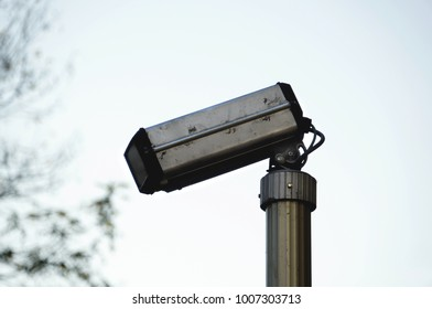 Classic design security camera. Surveillance cctv camera in street. White sky on background. Eye in the sky.