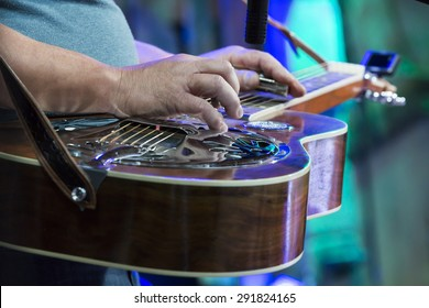 Classic Dobro guitar played my a master on concert. Focused on hand.
