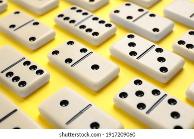Classic domino tiles on yellow background, closeup
