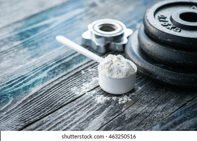 Classic dumbbell with protein powder on wooden table