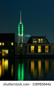Classic dutch houses along the river Rhine in the town of Alphen aan den Rijn, Netherlands. Illuminated communication tower in the background.
