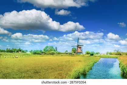 Classic Dutch Windmill in the field and a little stream with nice clouds in the blue sky. Traditional Dutch landscape.