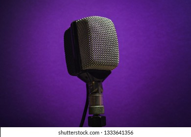 Classic dynamic microphone on a purple background. Vintage style