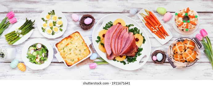 Classic Easter ham dinner. Top down view table scene on a white wood banner background. Ham, scalloped potatoes, eggs, hot cross buns, carrot cake and vegetables.