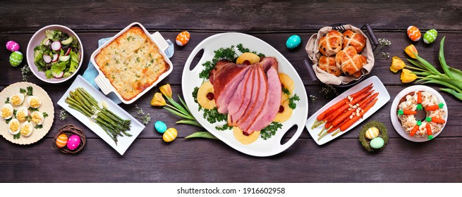 Classic Easter ham dinner. Top view table scene on a dark wood banner background. Ham, scalloped potatoes, eggs, hot cross buns, carrot cake and vegetables.