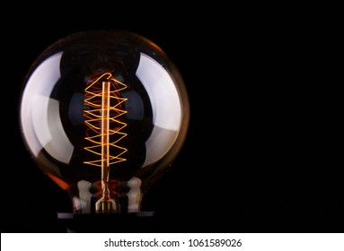 classic Edison light bulb on black background