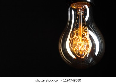 A classic Edison light bulb on dark background with space for text