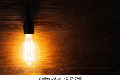 A classic Edison light bulb on wooden background switched on. retro edison light bulb