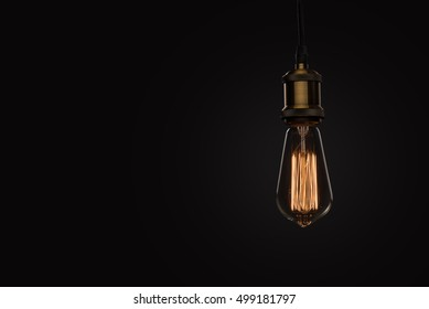classic Edison light bulb on black background with space for text