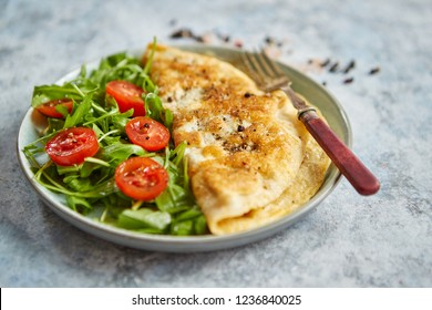 Classic egg omelette served with cherry tomato and arugula salad on side. Placed on white ceramic plate. Stone background with copy space.