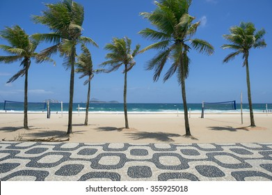 Classic empty view of Ipanema Beach Rio de Janeiro boardwalk with palm trees and blue sky and no people