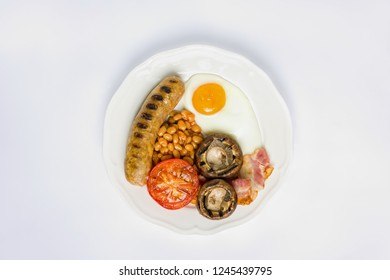 Classic English breakfast plated in a white plate on white background.