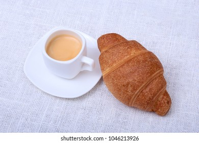 Classic espresso in white cup and croissant on white background. Top view.