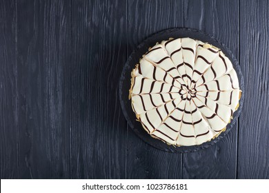 classic esterhazy torte on black slate plate on black wooden table, horizontal view from above