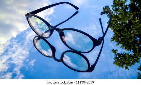 Classic Eye glasses put on mirror reflection of beautiful clear blue sky and tree for background.Freindly of Nature environment concept.
