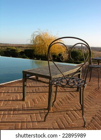 A classic fashionable metal chair and table with a luxurious view over a swimming pool