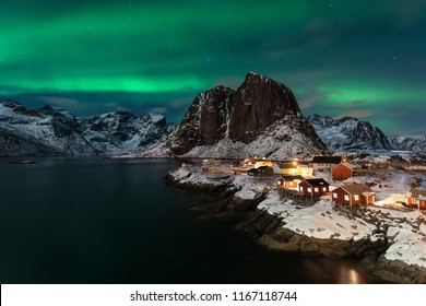 Classic fisherman village in Lofoten island Norway with a beautiful Northern Lights show and mountains