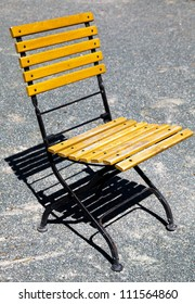 Classic French design outdoor folding chair with a black metal frame and wooden slats
