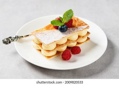 Classic french dessert millefeuille with vanilla cream and fresh berries.
