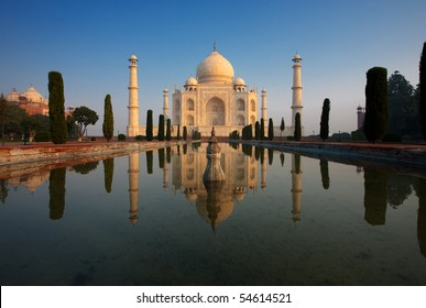 The classic front facade white marble of Taj Mahal glowing orange at sunrise centered and its reflection in a calm long water fountain with nobody present in Agra, India. Horizontal copy space