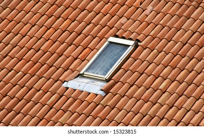A classic garret on a red tile roof.